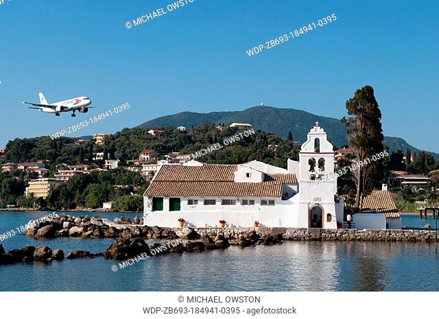 plane flying over Monastery of Panagia Vlahernon on Vlacherna Island off the Kanoni Peninsular Corfu Greece