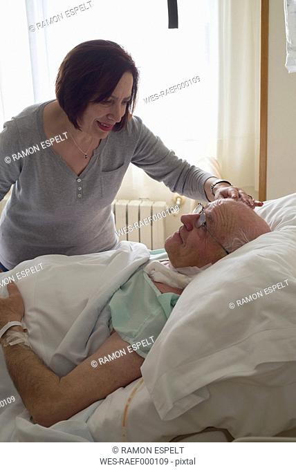 Senior woman caring for husband in hospital recovering after surgery