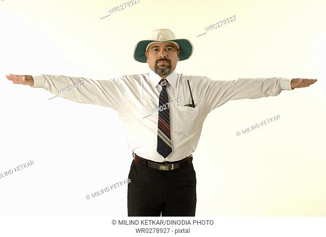 South Asian Indian cricket umpire indicating wide ball sign by outstretched both arms horizontally MR705G