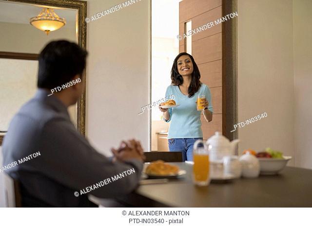 India, Woman walking toward man at breakfast table