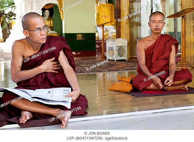 Myanmar, Yangon, Yangon. Two monks with one meditating and one reading a newspaper at the Shwedagon Pagoda in Yangon in Myanmar