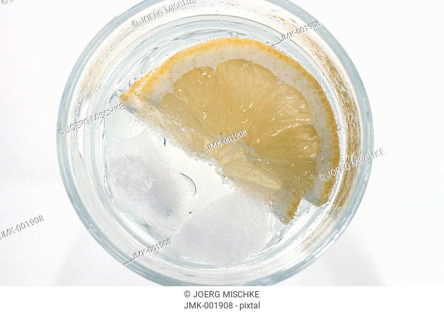 Mineral water, sparkling water, with ice cubes and twist of lemon in a glass