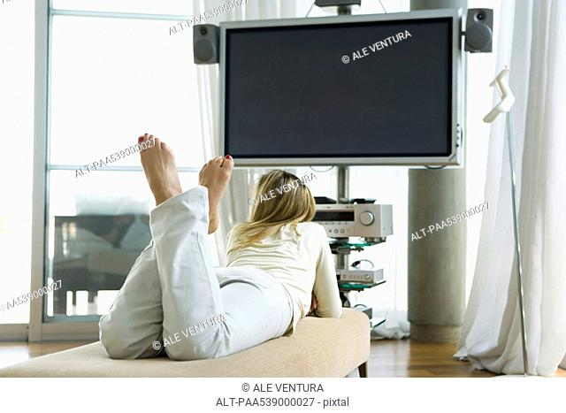 Female lying on stomach watching flat screen TV, rear view