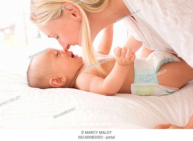 Mid adult woman nose to nose with baby son lying on bed