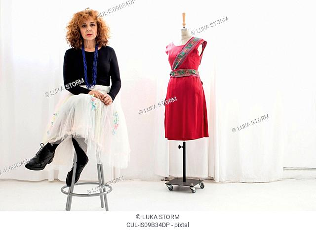 Woman sitting on stool by tailors dummy looking at camera