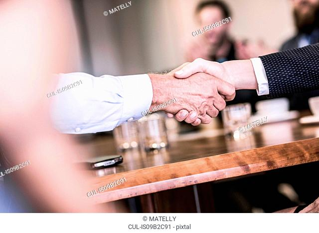 Close up of businesswoman and man shaking hands in board team meeting