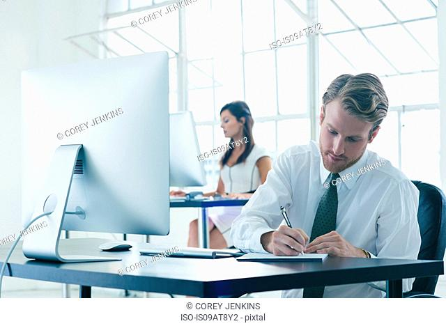 Business people working on computer by office window