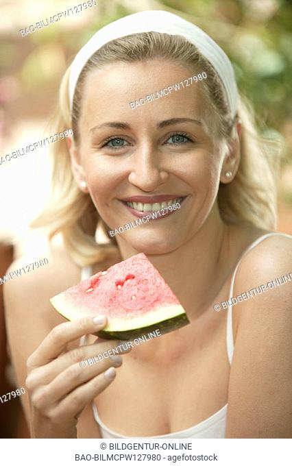 beauty young woman eating melon