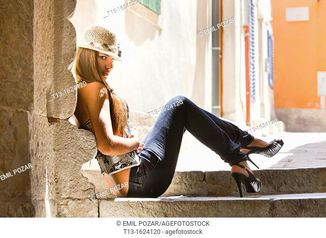 Young woman is sitting low on steps