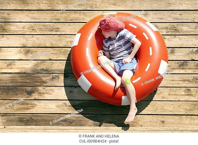 Boy sleeping in rubber ring on decking, Kraalbaai, South Africa