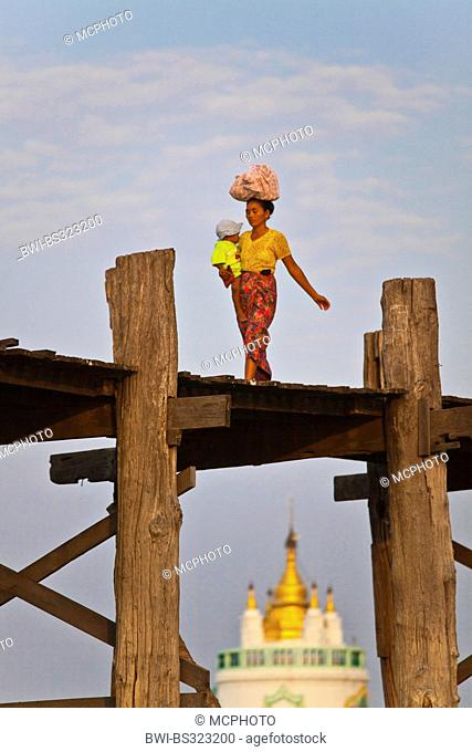 woman with litthle child on her arms using the teak U Beins Bridge to commute across the Taungthaman Lake, Burma, Amarapura