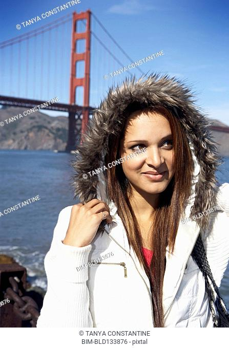 Mixed race woman standing in front of Golden Gate Bridge, San Francisco, California, United States