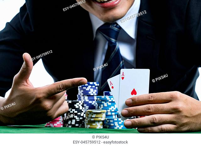 close up the young poker gambler use finger pointing to a pair of aces and smiling with glad to win the poker cards and holding bets a large stack