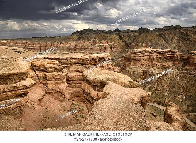 Tourists on cliff top at Charyn Canyon Park with clouds and Tien Shen mountains Kazakhstan