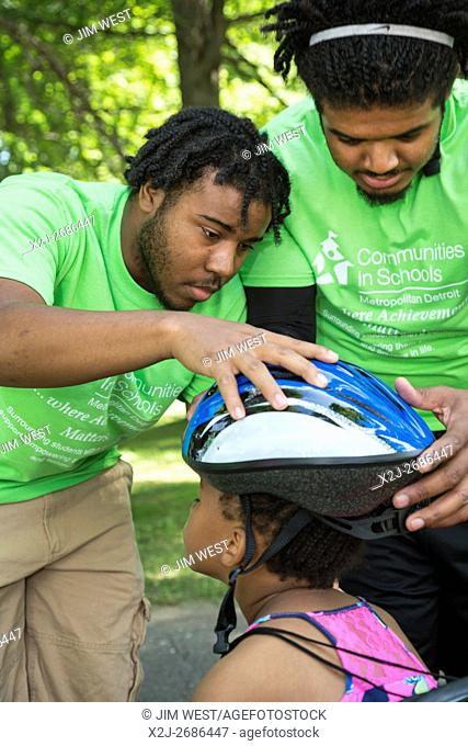 Detroit, Michigan - A girl is fitted with a bicycle helmet as Fiat Chrysler Automobiles distributes 350 free bicycles to students who have demonstrated good...
