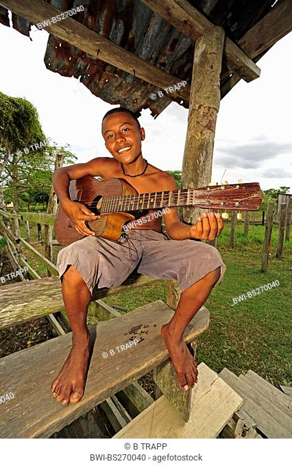 teenager sitting on the veranda of a wood house smiling with a guitar in hands, Honduras, La Mosquitia, Las Marias, Brus Laguna