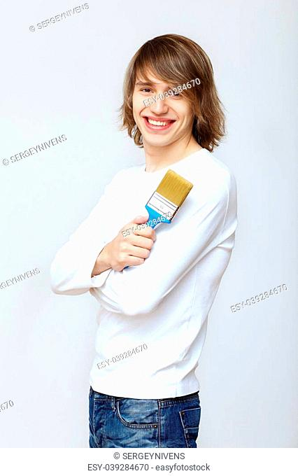 Portrait of young man with paint brushes