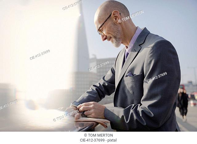 Businessman checking smart watch on sunny urban sidewalk, London, UK