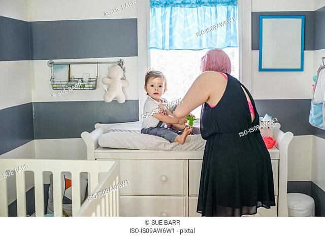 Mother getting baby son dressed on nursery day bed