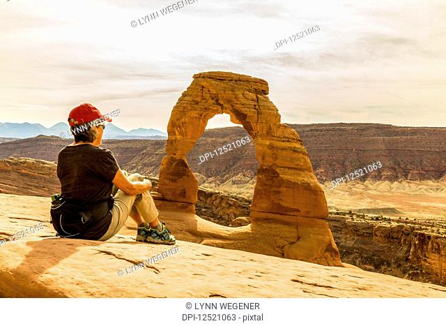 A female hiker sits enjoying the view of Delicate Arch in Arches National Park; Moab, Utah, United States of America