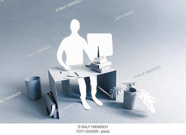 Paper businessman working at desk over gray background