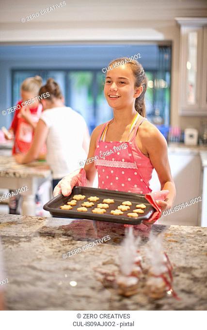 Teenage girls preparing biscuits in kitchen