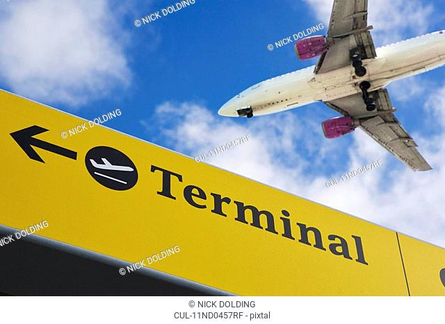 Plane flying over 'terminal' sign