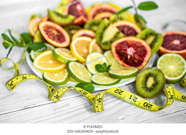 a variety of fruits and measuring tape on white background ,concept of health and nutrition
