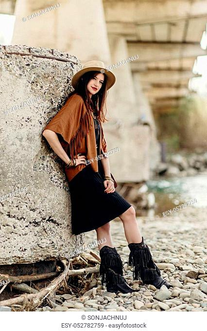 beautiful stylish boho woman with hat, fringe poncho and boots. girl in gypsy hippie look young traveler posing near river rocks in mountains