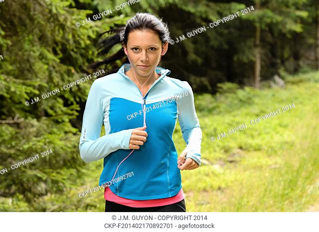 Running woman in forest fitness training outdoor
