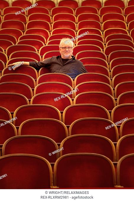 Portrait of confident mature stage designer sitting on seat in empty Vienna State Opera