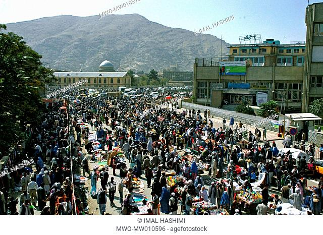 People of Kabul crowd at the center of the city where hundreds of street vendors sell their goods in the street The street is blocked due to heavy traffic jam...