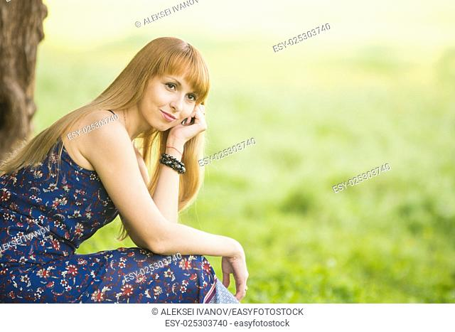 Beautiful young girl sitting against a tree on the background of blurred green grass and looks into the distance