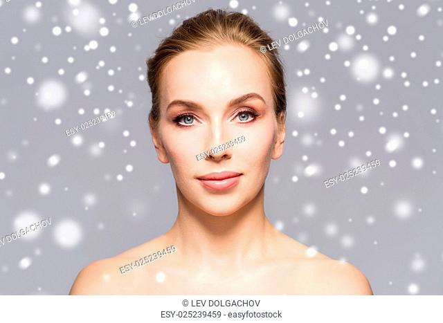 beauty, people, winter and health concept - beautiful young woman face over gray background and snow
