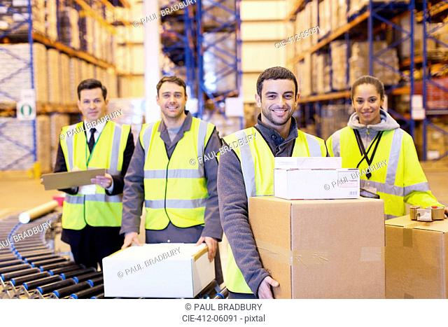Workers smiling by conveyor belt in warehouse