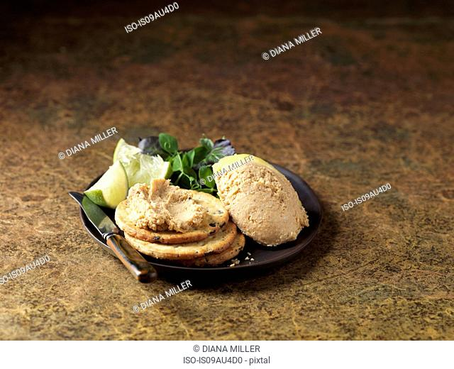 Orkney crab pate on crackers, lime wedges and mixed salad, dark background