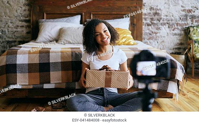 Young smiling african girl sitting near bed recording video blog about packing christmas gift box at home