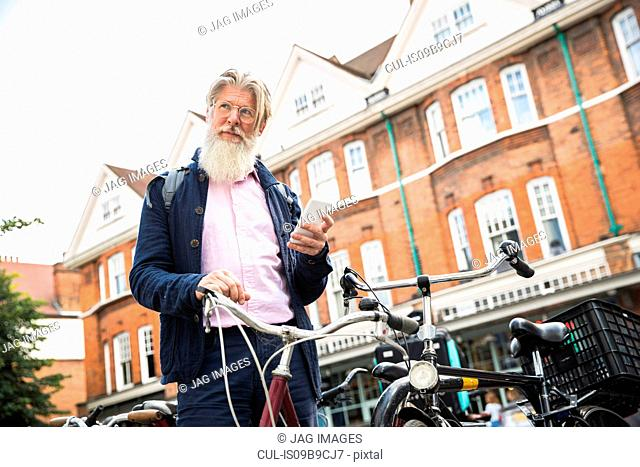 Mature man standing beside bicycle, holding smartphone