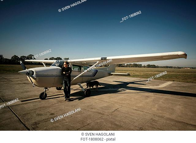 Male pilot standing at small propellor airplane on sunny tarmac