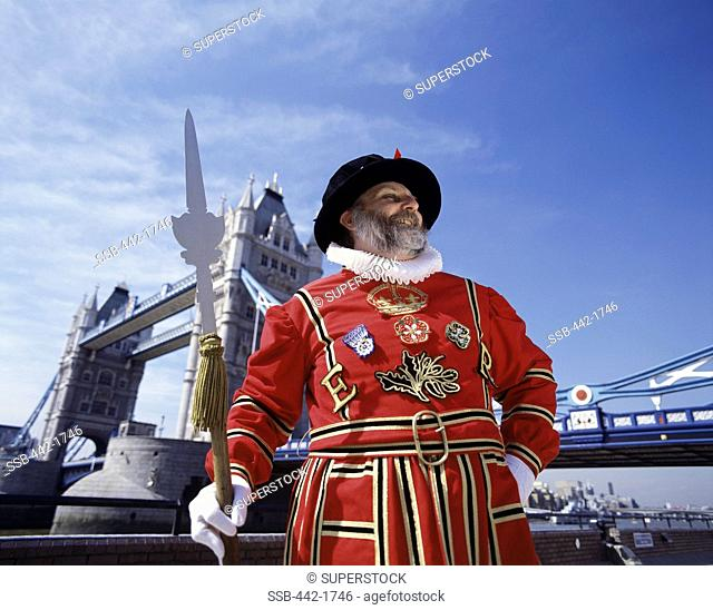Low angle view of a Beefeater standing with a bridge in the background, Tower Bridge, London, England