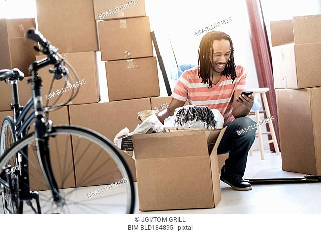Black man unpacking boxes in new home