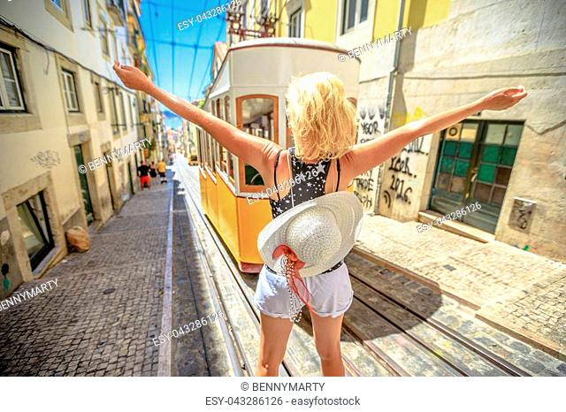 Happy woman with open arms in Lisbon, Portugal, Europe. Blonde caucasian female enjoying in front of Bica Funicular. Elevador or Ascensor da Bica is a popular...