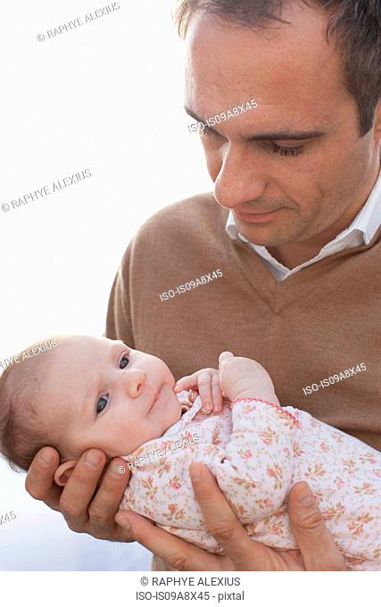 Father holding newborn baby daughter