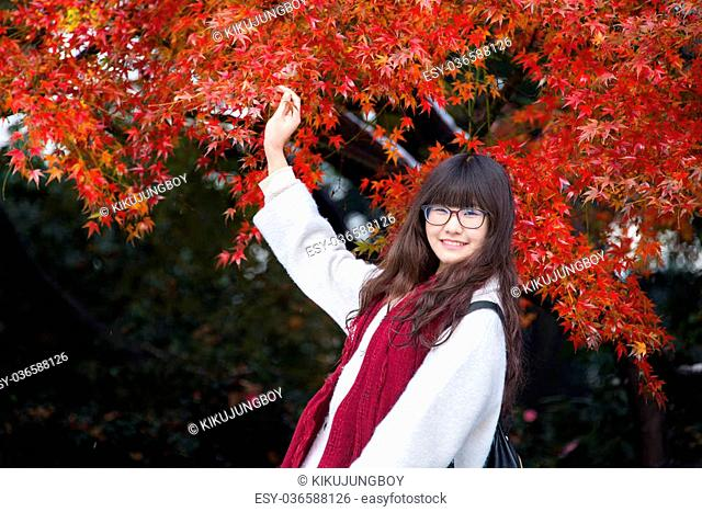 Young Chinese woman in action with autumn leaves