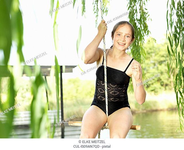 Teenage girl sitting on rope swing over lake