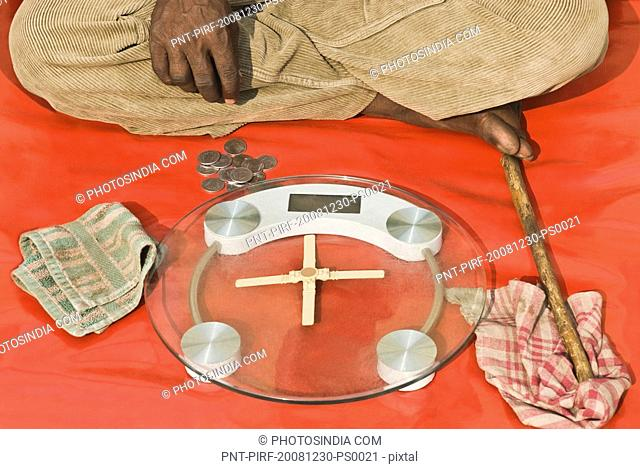 Man sitting with a weighing scale, Delhi, India