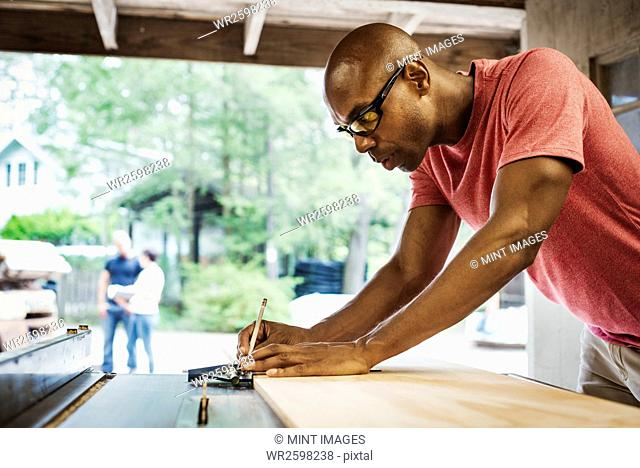 Man wearing glasses working in a lumber yard