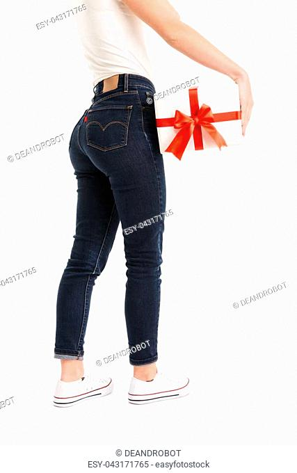 Half portrait of a woman dressed in t-shirt and jeans holding present box isolated over white background