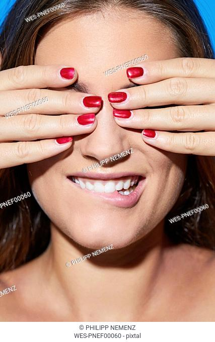 Beautiful young woman with red fingernails covering her eyes