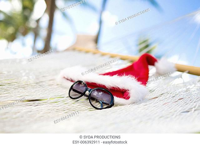 vacation, christmas and holiday concept - picture of hammock with santa helper hat and sunglasses